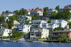 Swedish waterside housing Bromma. Waterside houses and jetty with motorboat in a suburban residentual area at Lake Mälaren, Bromma, Stockholm, Sweden Royalty Free Stock Image
