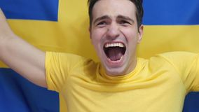 Swedish Young Man Celebrates holding the Flag of Sweden in Slow Motion. High quality royalty free stock photos
