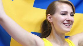 Swedish Young Woman Celebrates holding the Flag of Sweden in Slow Motion. High quality stock photos