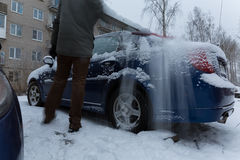 Sweep snow from the car in winter time lapse video. Sweep snow from the car in winter timelapse. men sweeps the snow from his car in the parking lot Stock Photography