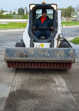 Sweeper attachments mini excavator. The sweeper sweeps, collects and dumps dirt and debris Stock Photos