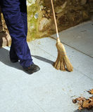 Sweeper on the street sweeping with his broom autumn leaves Stock Images