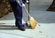 Sweeper in the street sweeping up with her broom Stock Image