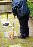 Sweeper in the street sweeping up with her broom Stock Images