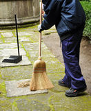 Sweeper in the street sweeping up with her broom Royalty Free Stock Images