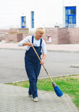 Sweeper worker cleaning city street with broom tool. Stock Images
