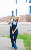 Sweeper worker cleaning city street with broom tool. Royalty Free Stock Photos