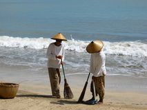 Sweepers on Bali. Balinese beach sweepers Royalty Free Stock Images