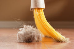 Sweeping. A broom about to sweep up a giant ball of dust royalty free stock images
