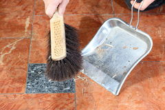 Sweeping. Hands holding broom and dust pan sweeping up Royalty Free Stock Photo