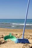Sweeping the beach (irony). Broom and shovel sweeping the beach (irony Stock Images