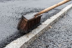 Sweeping broom for asphalting works. Broom for asphalting works in road construction - close-up Stock Photo