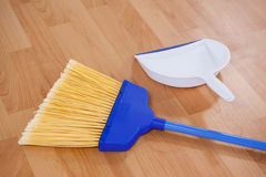 Sweeping broom and dustpan on wooden floor Royalty Free Stock Image