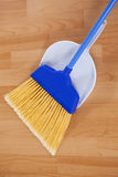 Sweeping broom with dustpan on wooden floor Royalty Free Stock Images