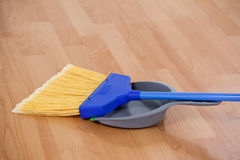 sweeping broom with dustpan on wooden floor royalty free stock photography