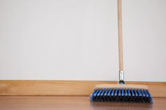 Sweeping broom with wooden handle on floor. Against wall Stock Image