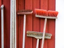 Sweeping brushes near the wall of wooden house Stock Photography