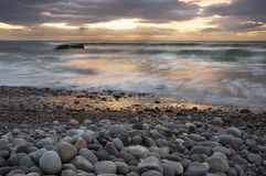 Sweeping clouds, rounded pebbles, and the sea at sunrise with WW2 defence bunker Stock Photos
