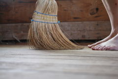 Sweeping the Floor. Female in bare feet using a broom to sweep a dirty floor Royalty Free Stock Photos