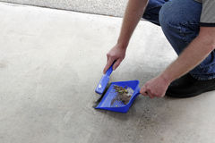 Sweeping Floor Dirt into a Dustpan. Male crouched down sweeping a cement garage floor of dust and debris with a small broom into a dustpan. Rubbish on a garage Stock Photography