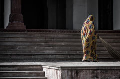 Sweeping the floor. A shot of a woman in Indian traditional clothing sweeping the floor Royalty Free Stock Photo