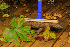 Sweeping leaves. On a garden patio in autumn Royalty Free Stock Photography