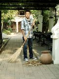 Sweeping Leaves. A man sweeping leaves with the broom Stock Photo