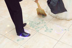 Sweeping Money. Groom with broom sweeping money Royalty Free Stock Photography