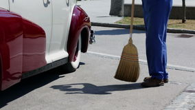 Sweeping a parking lot with a brom and vintage car stock video