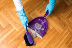 Sweeping parquet floor with brush and dustpan Royalty Free Stock Image
