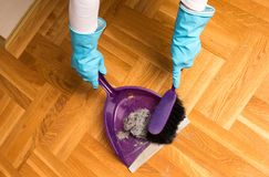 Sweeping parquet floor with brush and dustpan Royalty Free Stock Photo