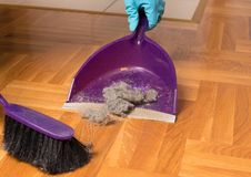 Sweeping parquet floor with brush and dustpan Stock Photography