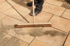Sweeping Paving Area. Man sweeping patio after making repairs Stock Photo