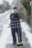 Sweeping snow. Man sweep new snow off sidewalk in winter Royalty Free Stock Image