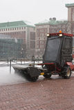 Sweeping the snow. Chain clad snow sweeper cleaning a brick sidewalk Royalty Free Stock Photos