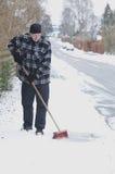 Sweeping snowy sidewalk. Man sweeping snowy sidewalk in the winter with a broom Royalty Free Stock Photos