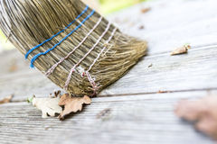 Sweeping wooden patio. Closeup of sweeping autumn leaves off wooden patio with a broom Stock Photography