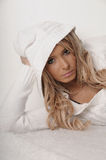 Sweet. Headshot of a beautiful blond model in a lying position wearing a woolen knitted top with hood up in white Royalty Free Stock Photos