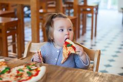 Sweet adorable child baby girl eating pizza at a restaurant. Sweet adorable child baby girl eating pizza at a restaurant stock photo