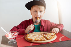Sweet adorable child, boy in stylish cap and red shirt eating pizza and ice-cream at a restaurant. Fashion little boy having break. Fast at cafe. People and Stock Images