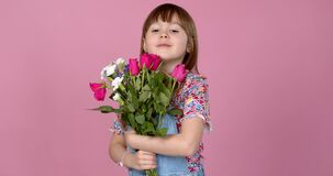 Sweet adorable young little girl holding bunch of fresh spring flowers. Wearing dungarees