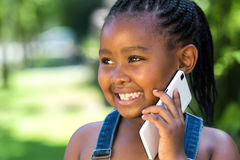 Sweet african girl having conversation on smart phone. Royalty Free Stock Photos