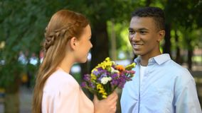 Sweet Afro-American teen boy presenting bunch of flowers to shy girlfriend. Stock footage stock video