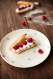 Sweet afters with fresh raspberries on wood table Royalty Free Stock Images