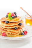 Sweet american pancakes with maple syrup and berries. Closeup of sweet american pancakes with maple syrup and berries royalty free stock photo