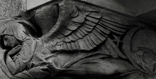 Sweet angel in the city. Shot in black and white detail of the sculpture on the facade of this historic building representing some characters / animals / plants stock images