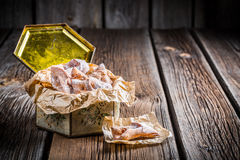 Sweet angel wings in vintage box. On old wooden table Royalty Free Stock Photography