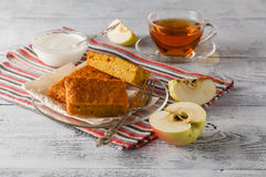 Sweet apple cake served with apples and tea cup on wooden plate Royalty Free Stock Images