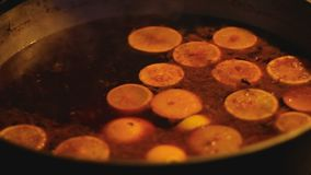 Sweet aromatic mulled wine boiling on fire, traditional winter beverage. Stock footage stock footage
