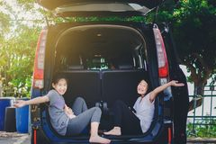 Asian happy Girl relax on car after long trip. Sweet Asian happy Girl relax on car after long trip stock image